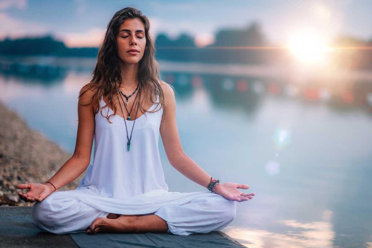 Woman sits in Lotus Pos on edge of lake
