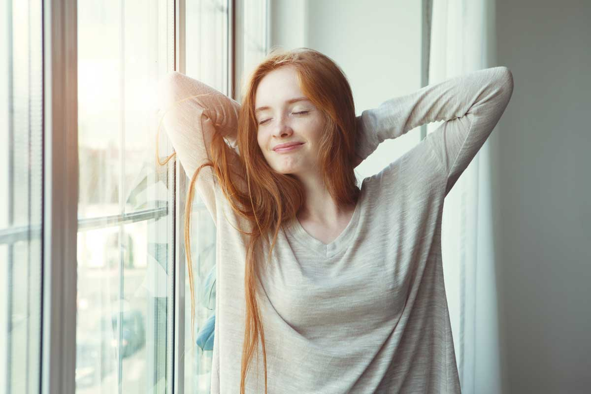 Red haired woman stretches whilst smiling by window