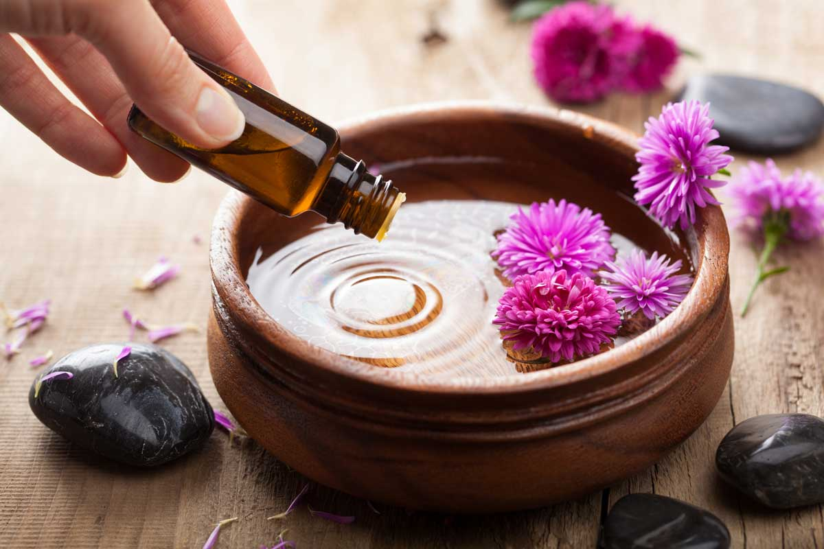 Pouring essential oils into a dish of water and flowers