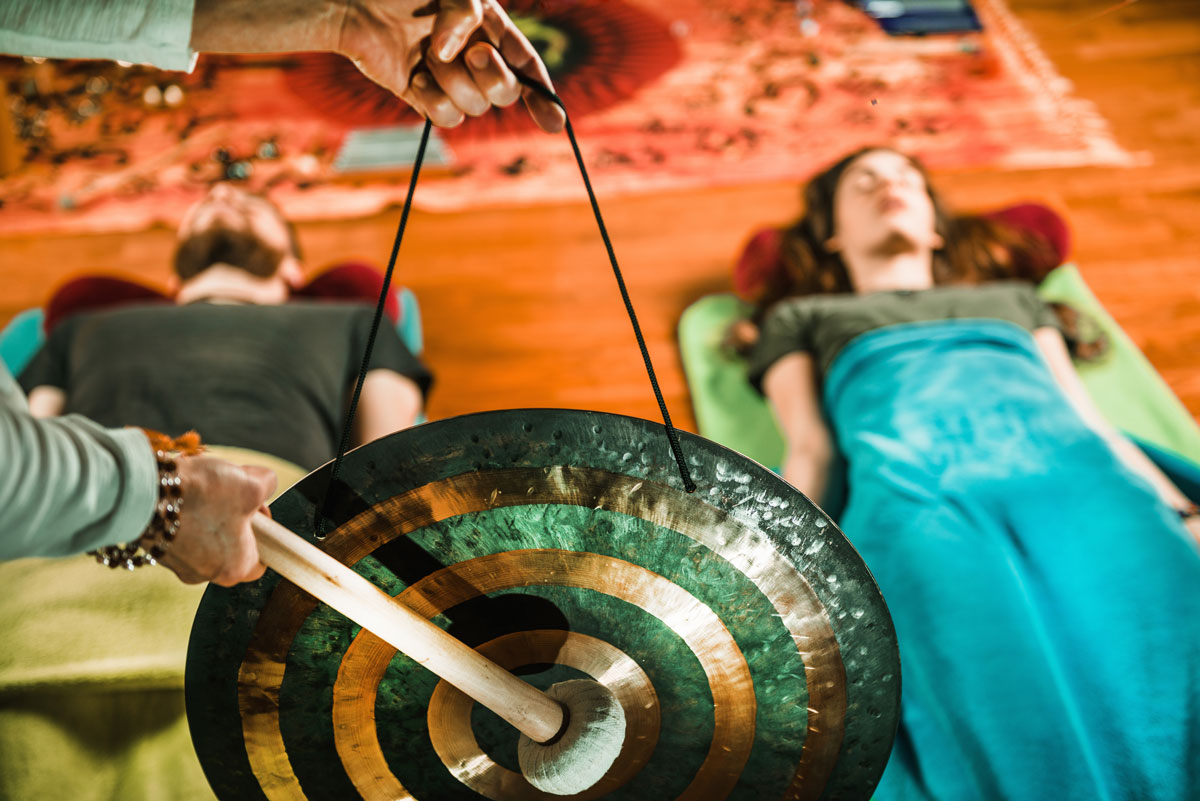 Girl and guy lie on the floor whilst doing Sound Bath Healing