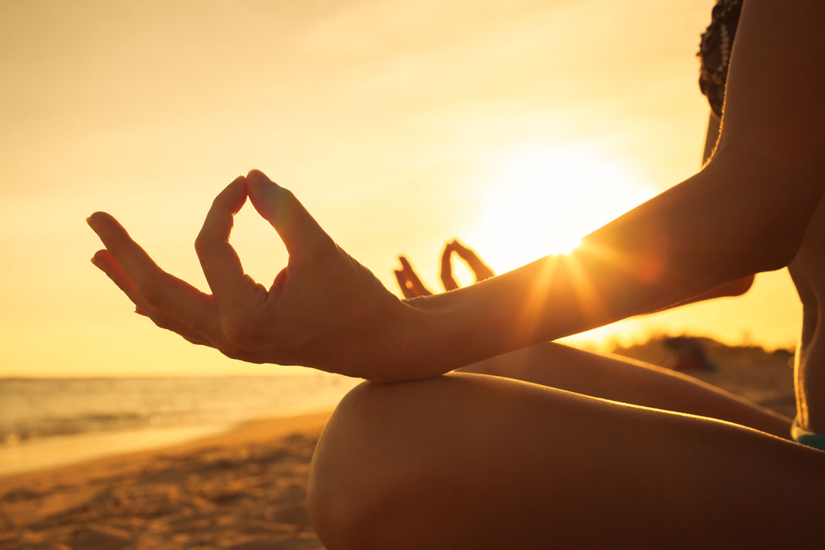 Mudra hand postures by the beach