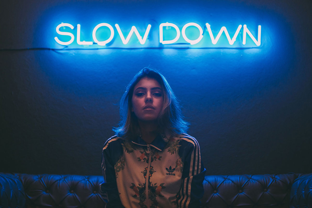 """Girl in floral Adidas top sits on sofa under """"Calm Down"""" neon sign, sign, doing Long Deep Breathing for Pranayama"""