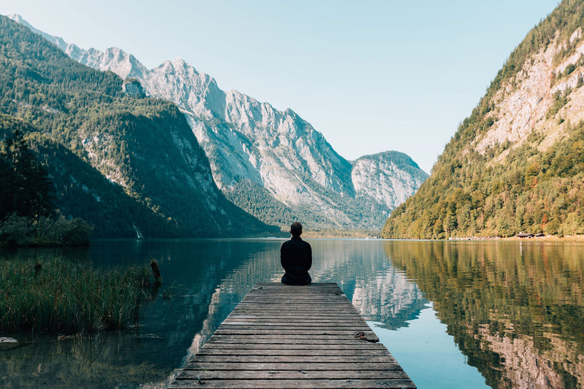 Man practises meditation by a calm lake underneath beautiful mountains