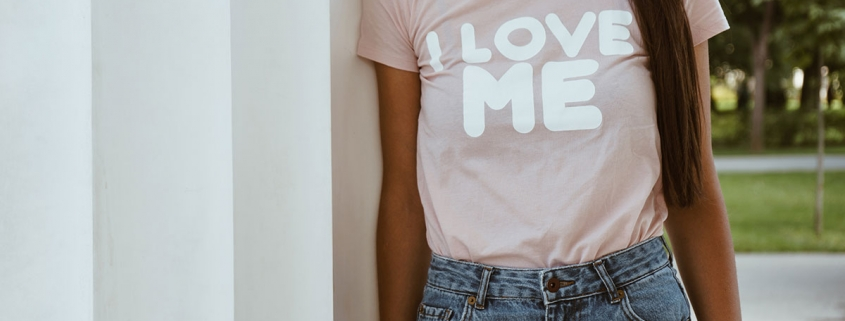 """Yoga girl wearing light pink T-shirt which says """"I LOVE ME"""""""