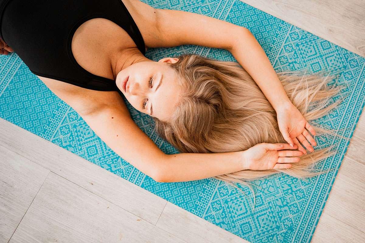 Girl on Yoga Mat practising Sat Kriya Kundalini Yoga Mediation