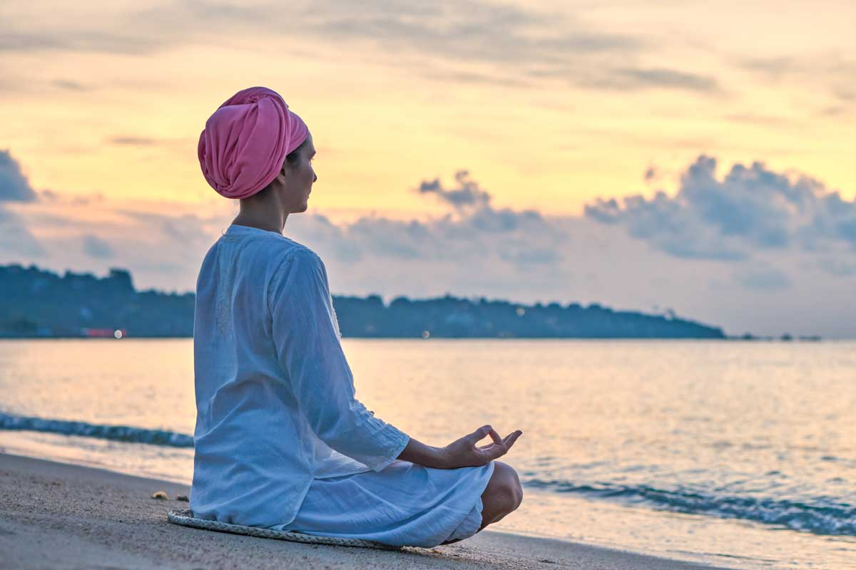 Woman sits meditating on beach at sunset