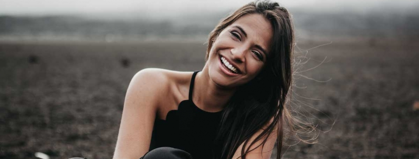 Woman sits in field, smiling