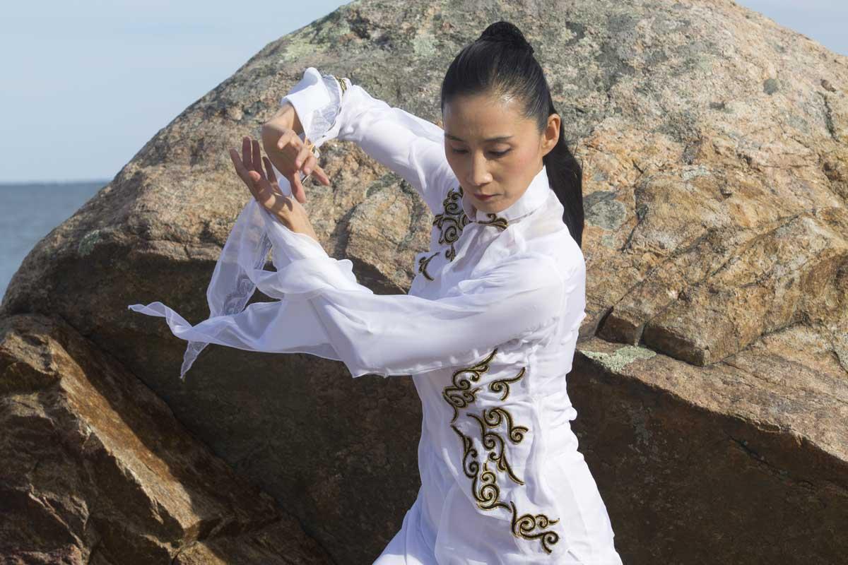 Lady in white practising Qigong Kundalini Yoga