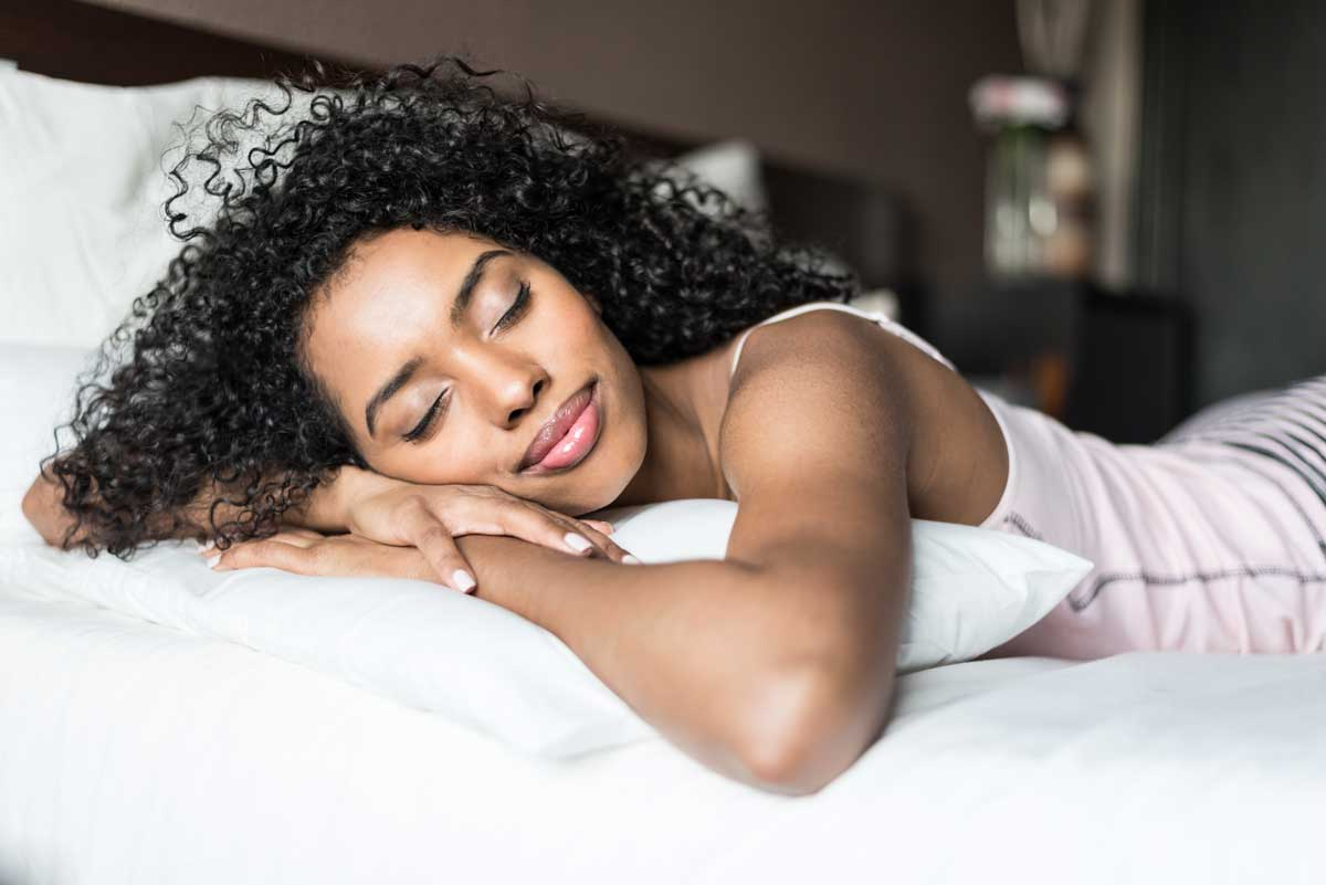Woman lays on bed smiling