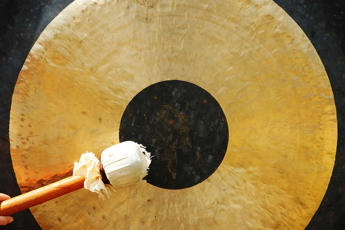 Close up of a mallet stricking a gold gong with black circle in centre.