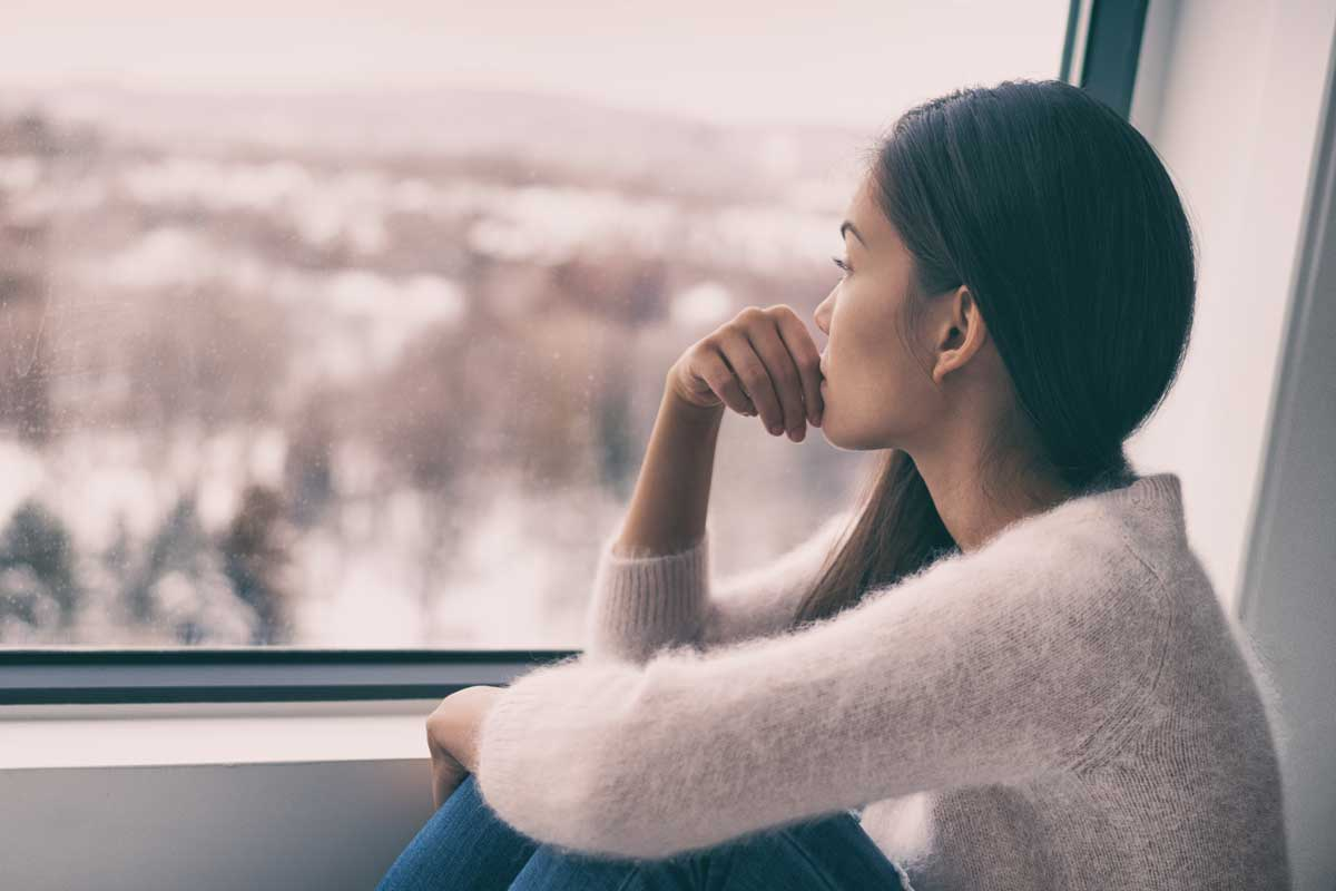 Woman sits staring out of window