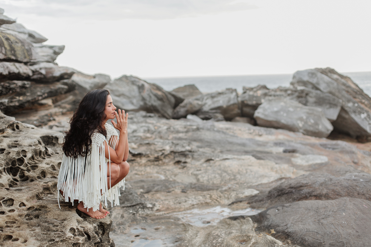 Woman sits on rock by the sea with hands in prayer position