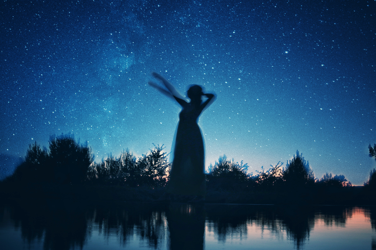 Silhouette of woman dancing under starry sky near lake