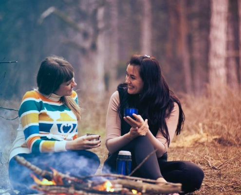 Two friends chat sitting around a camp fire in woods