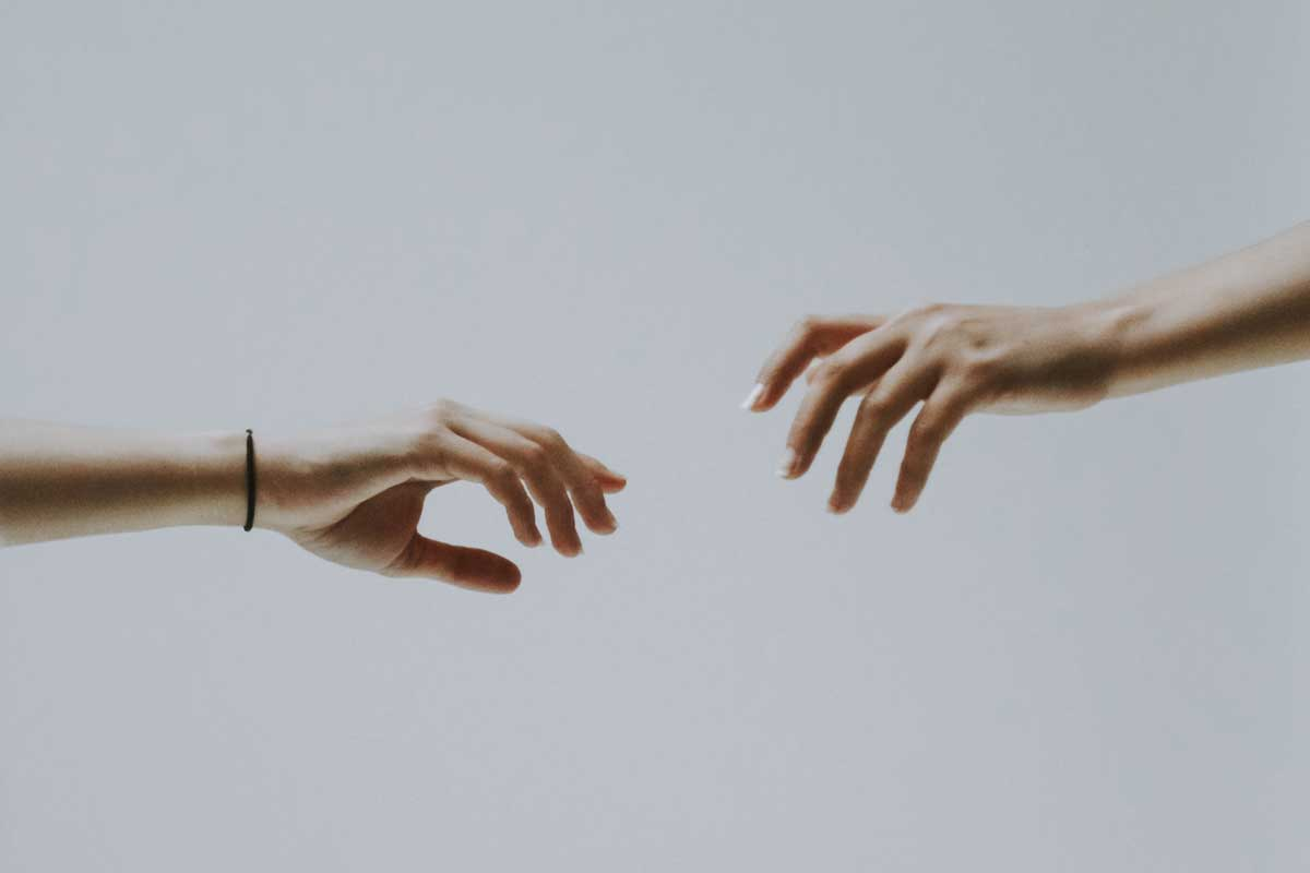 Woman and Man's hands recah out to touch each other