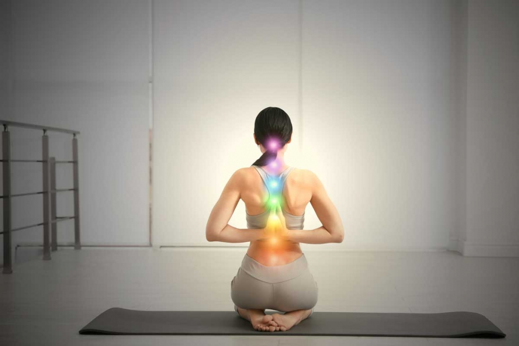 Woman sits in rock pose with glowing chakras along her spine