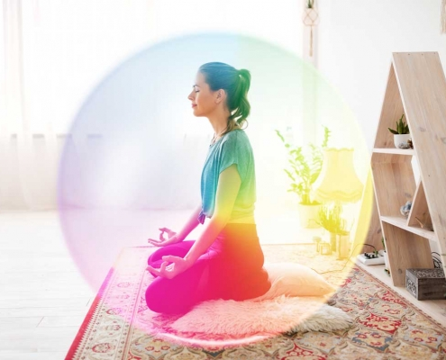 Woman sits in room meditationg surrounded by bright colourful aura