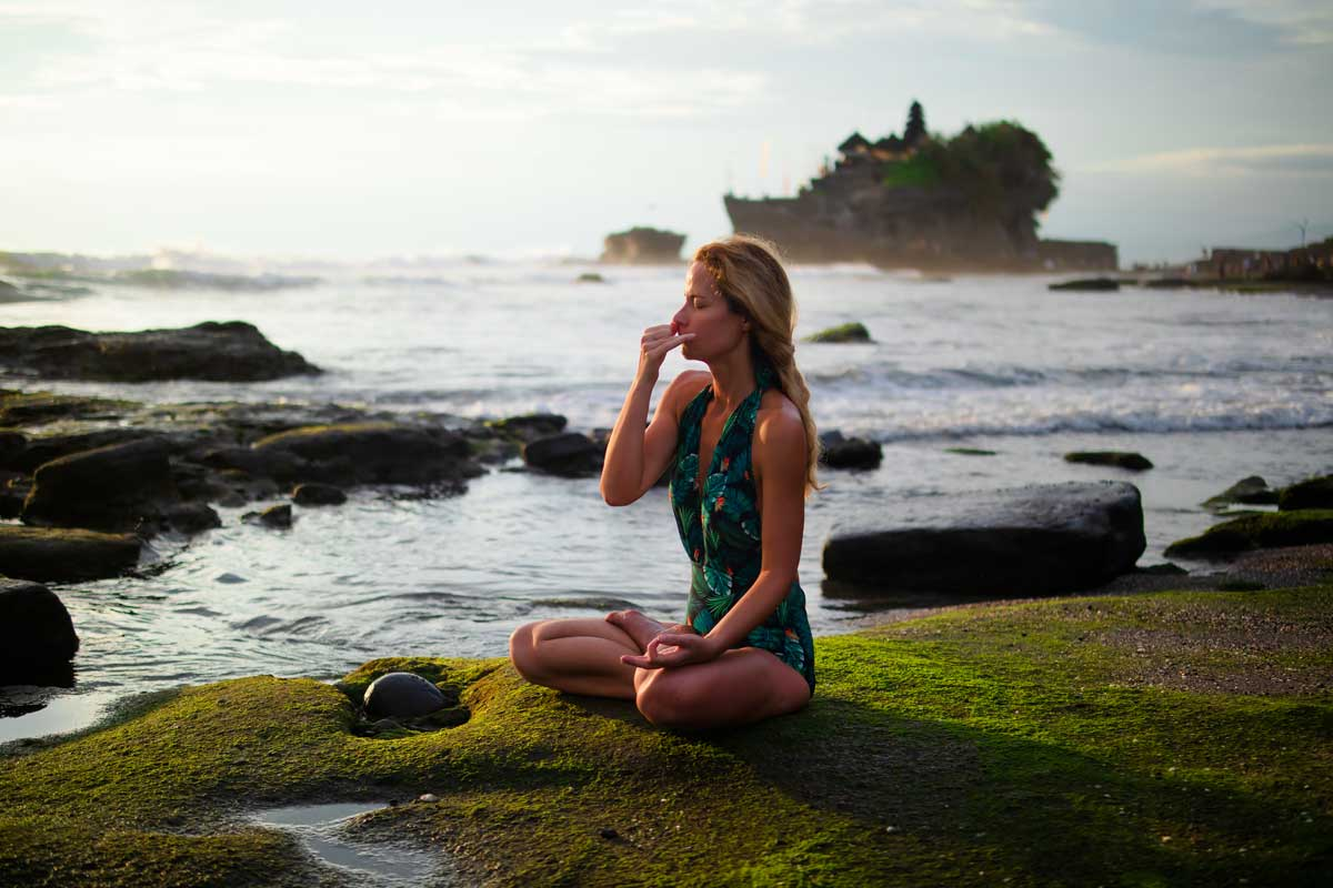 Woman practices pranayama by on rock the sea