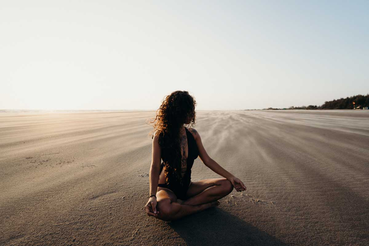 Woman sits meditating in stillness on beach