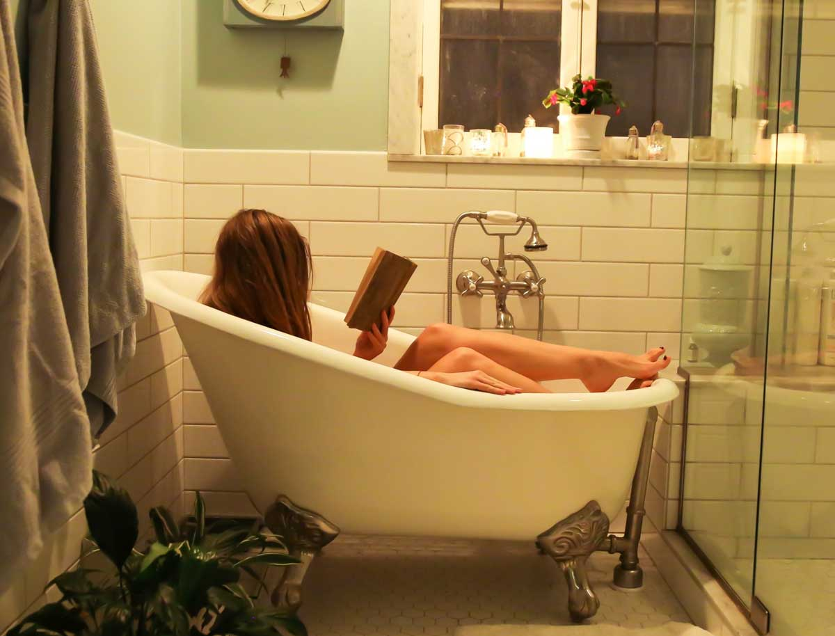 Woman reads whilst taking a bath