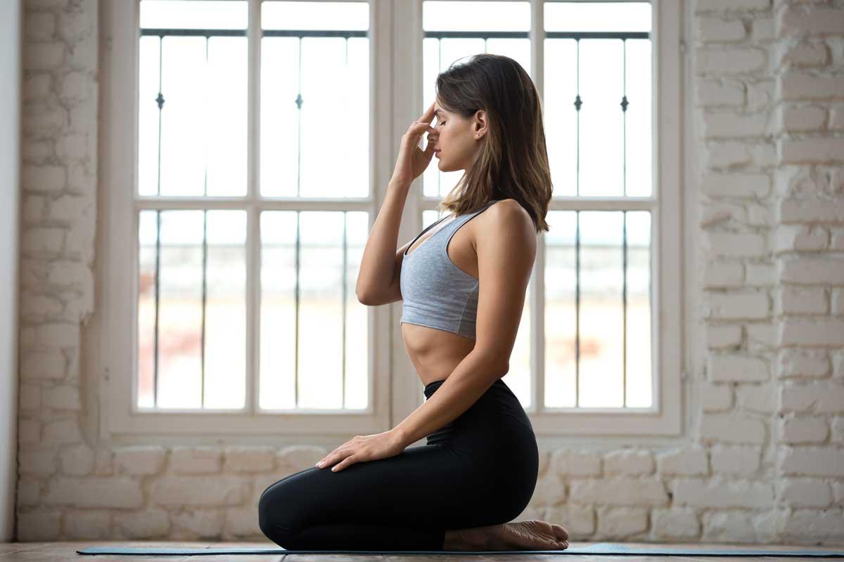 Woman practices Pranayama on yoga mat