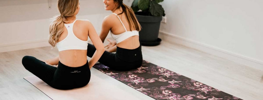 Two women sit on yoga mats, chatting to each other