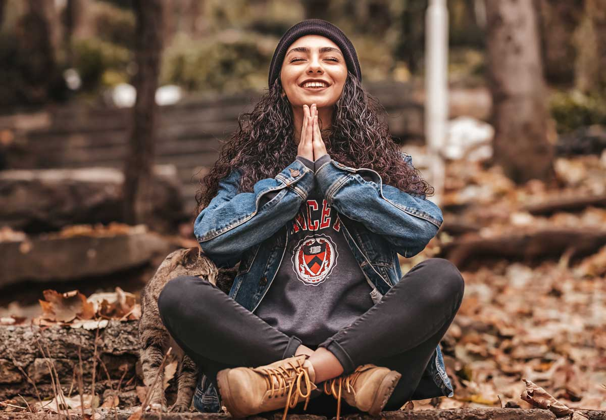 woman sits cross-legged on leaves with hands in prayer position, smiling