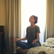 Woman sits on bed meditating