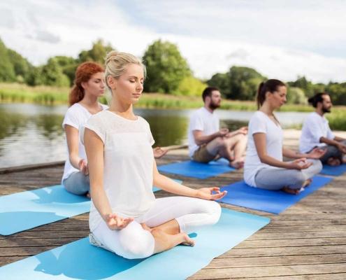 Group of people sit meditating, wearing white