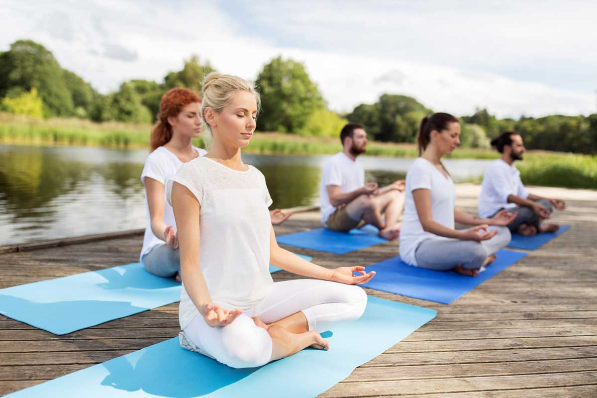 Group of people sit meditating, wearing white