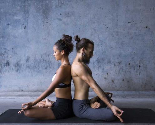 Couple sit meditating back to back