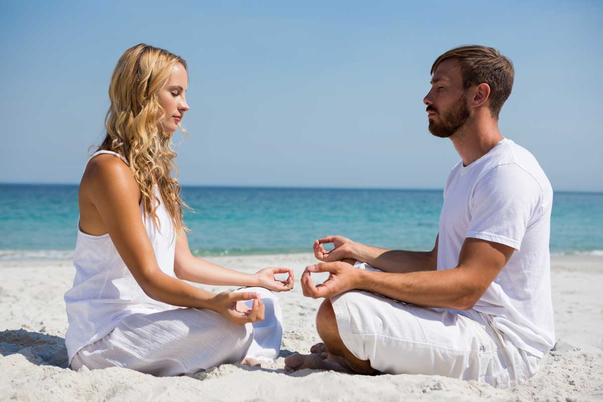 Woman & man sit opposite each other, meditating on beach