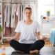 Woman sits on bedroom floor meditating