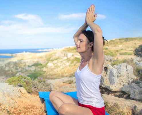 Woman meditates on cliff