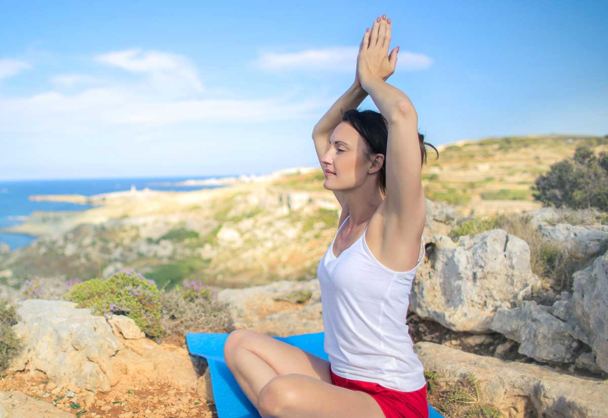 Woman meditates on cliff
