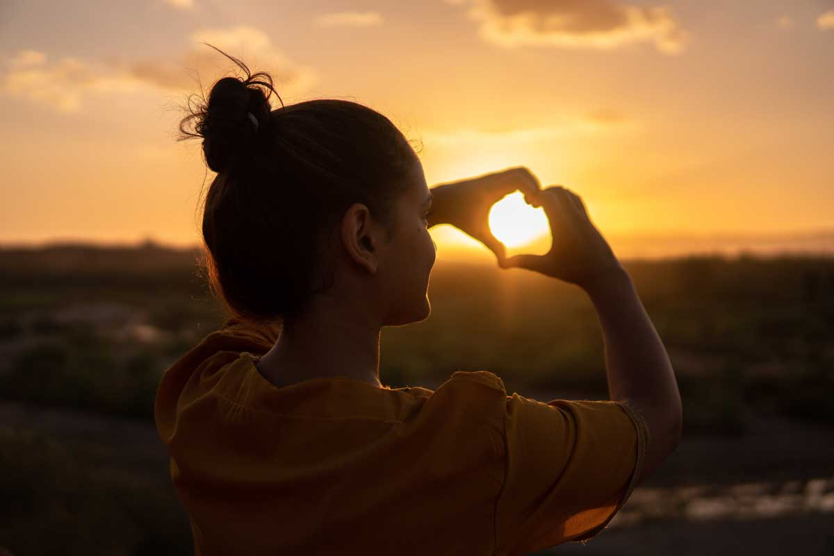 Woman makes heart shape with hands infront of sunset
