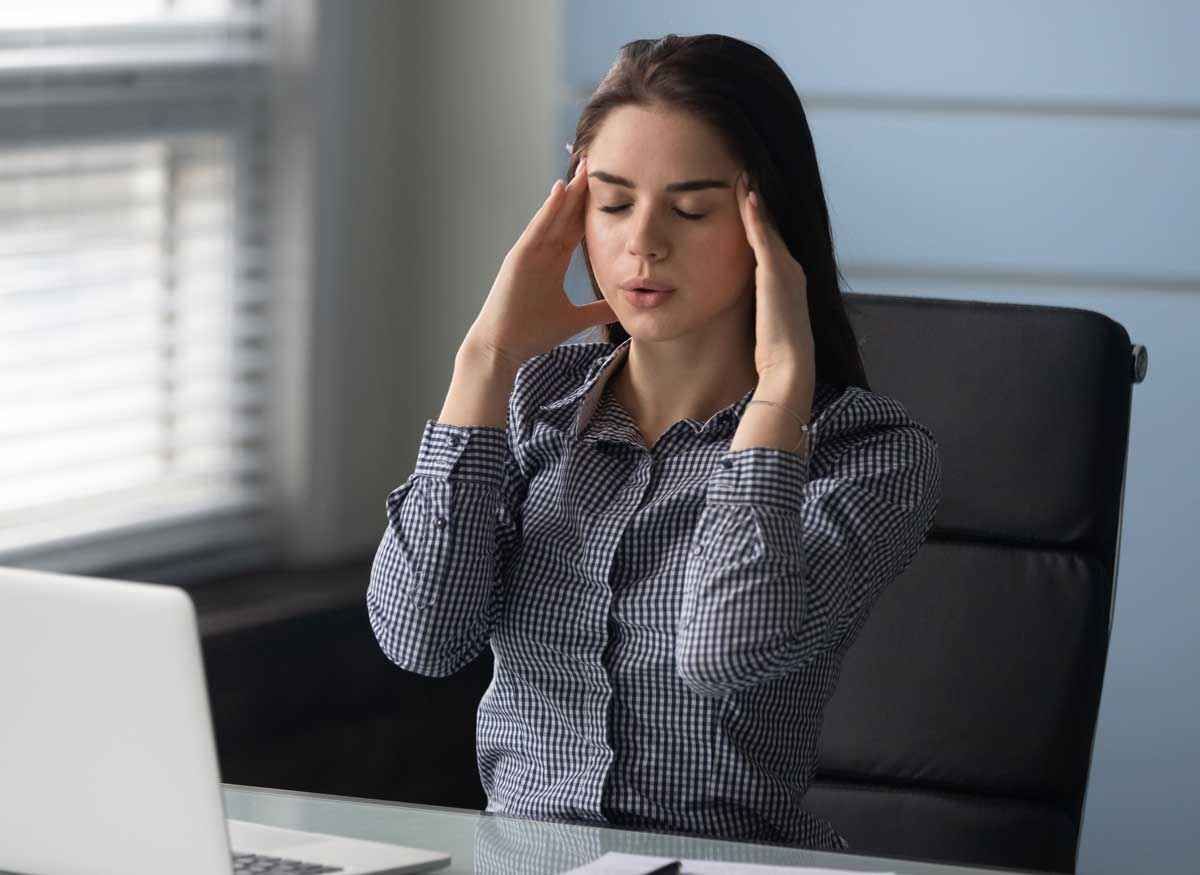 Woman practices breathwork at desk