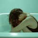 Woman sitting hunched over in bathtub