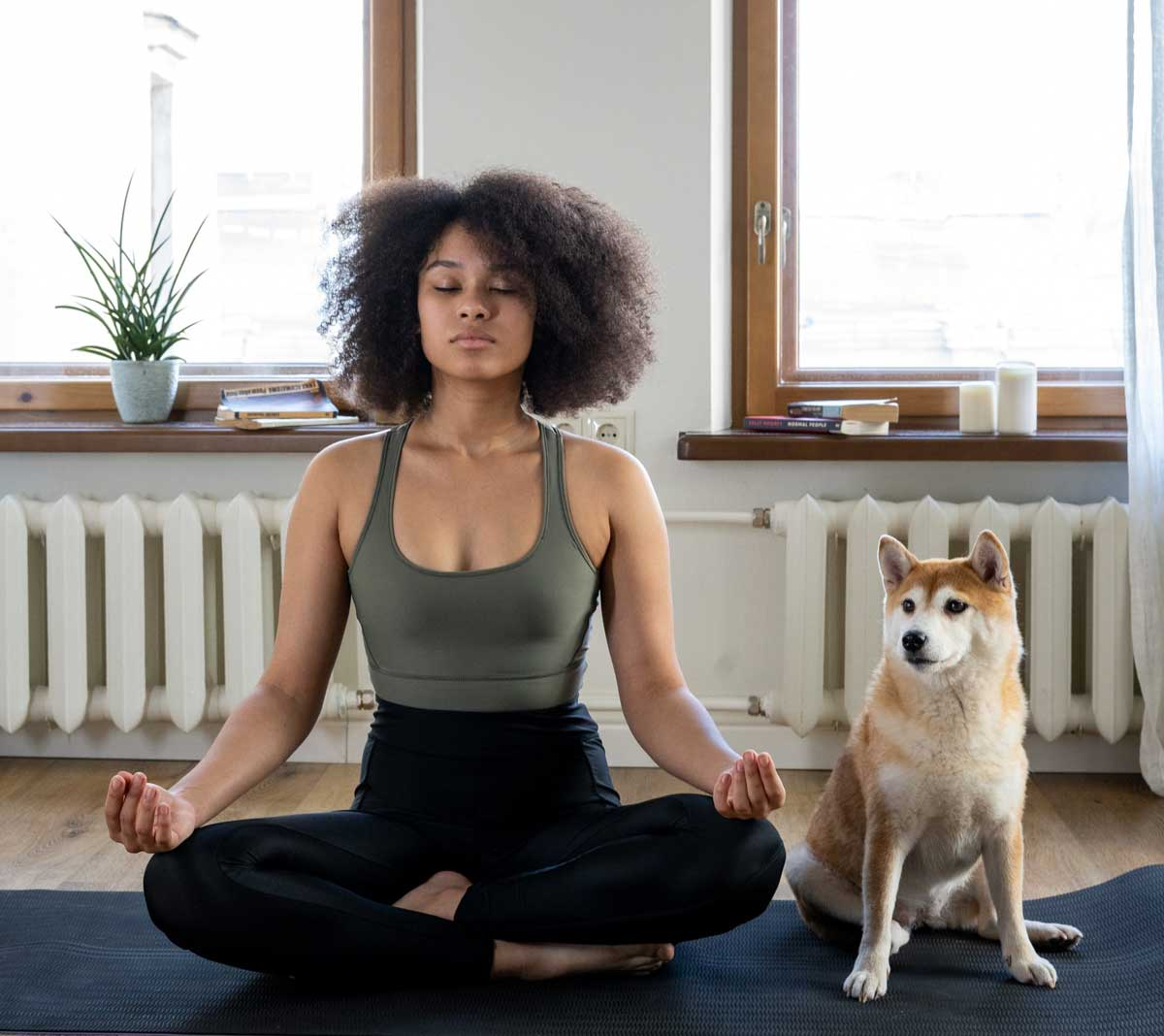Woman sits meditating at home, with dog