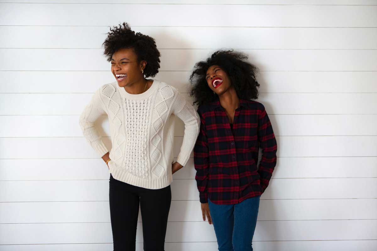 Two women stand laughing together
