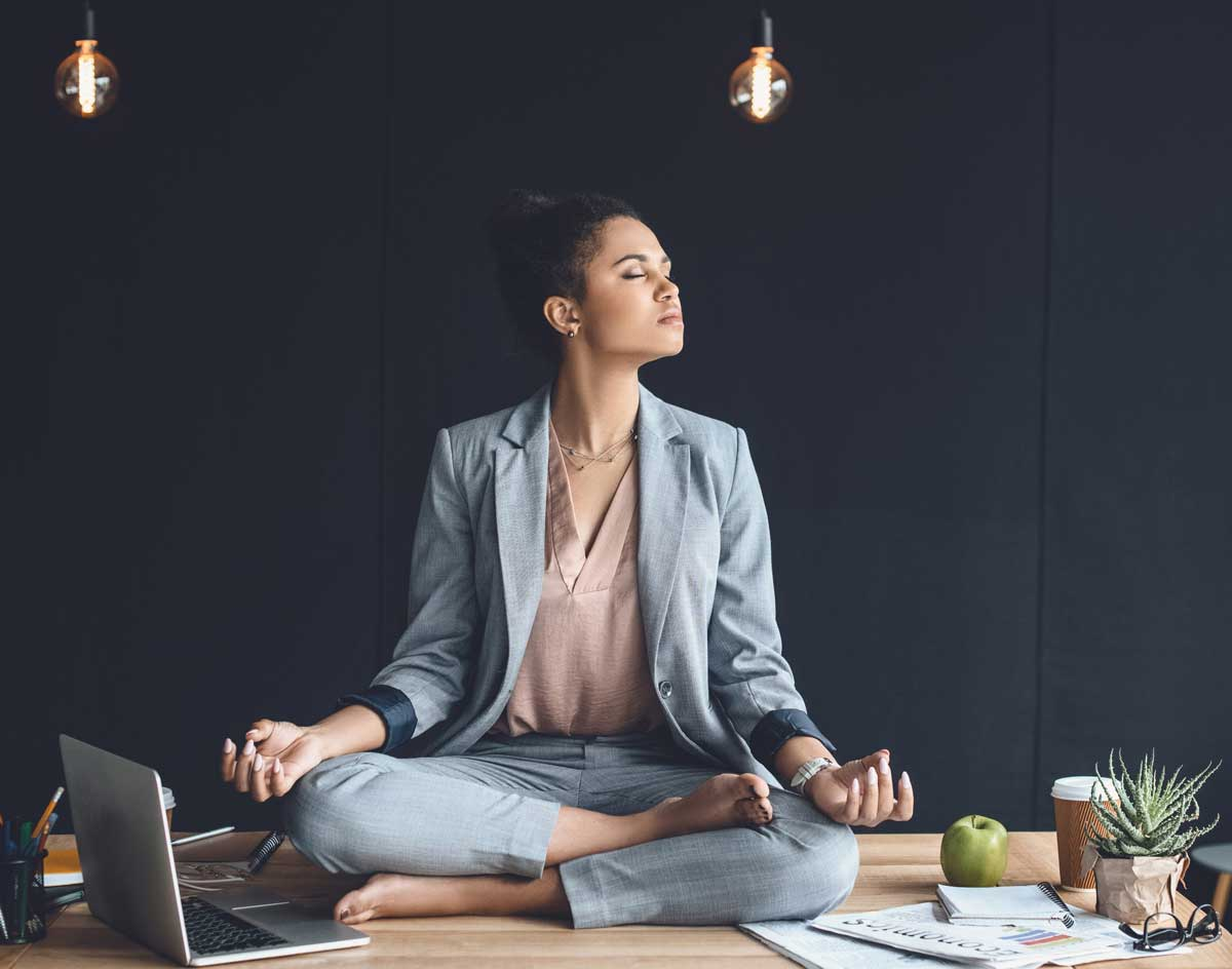 Woman sits meditating on desk