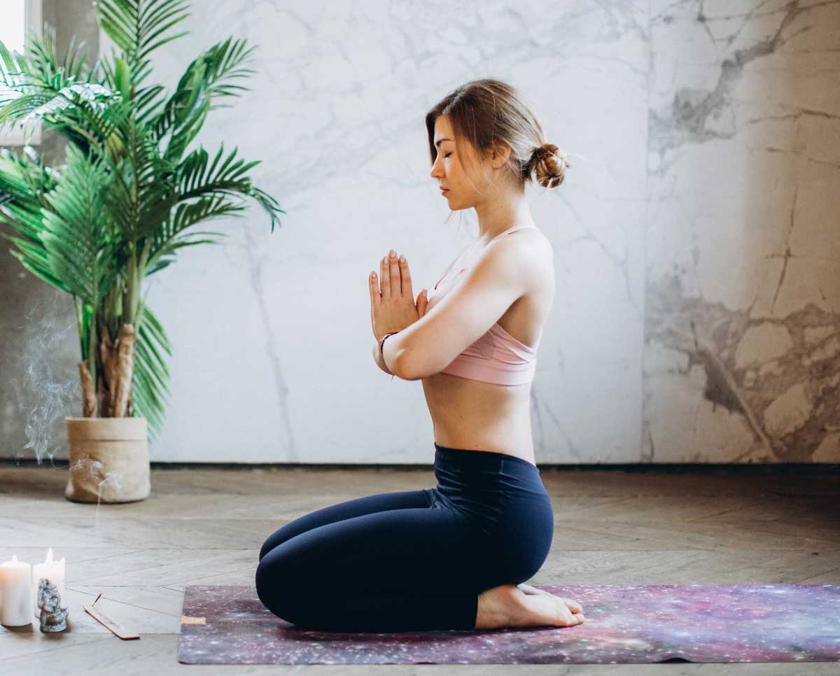 Woman sits in rock pose on yoga mat