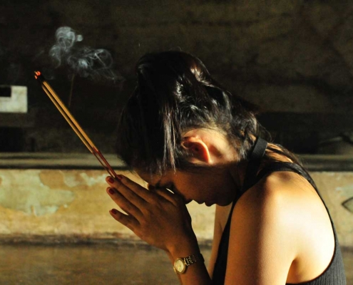 Woman sits in prayer, holding incense