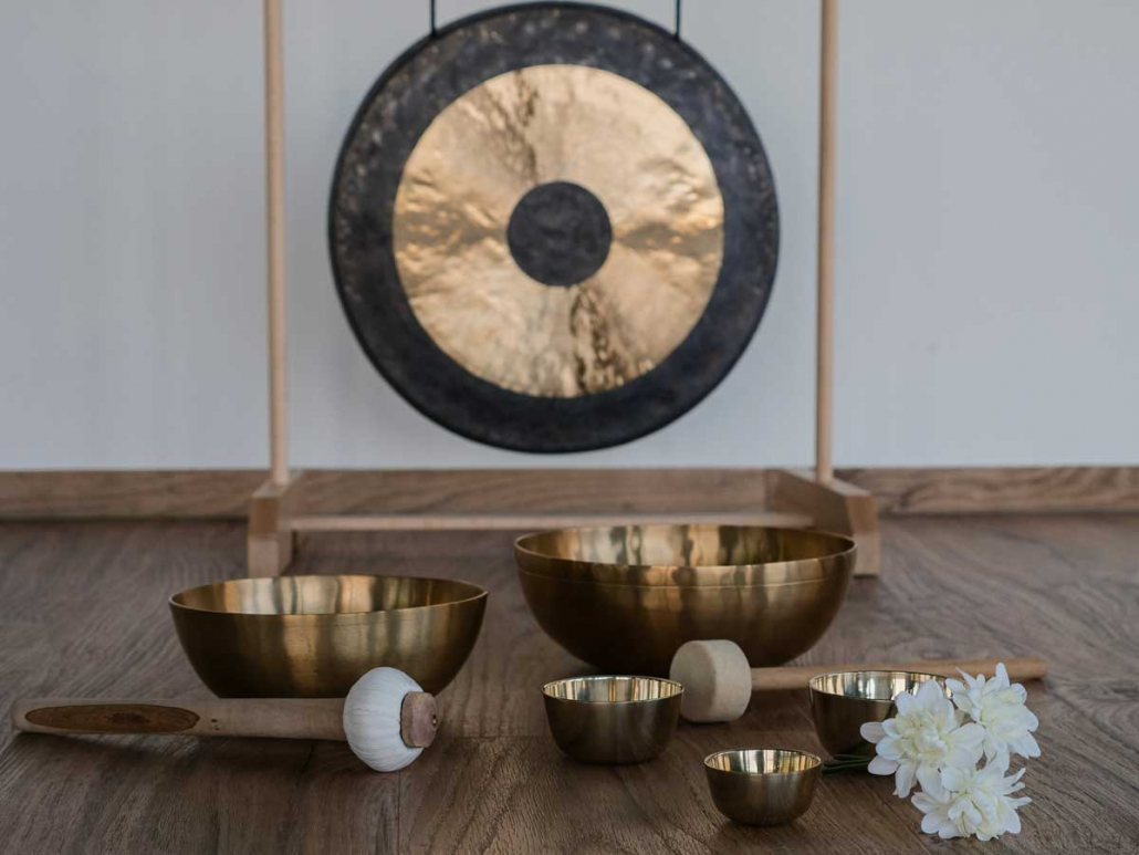 Brass gong with Tibetan singing bowls on flor