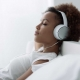 Woman relaxing in bed with head phones on